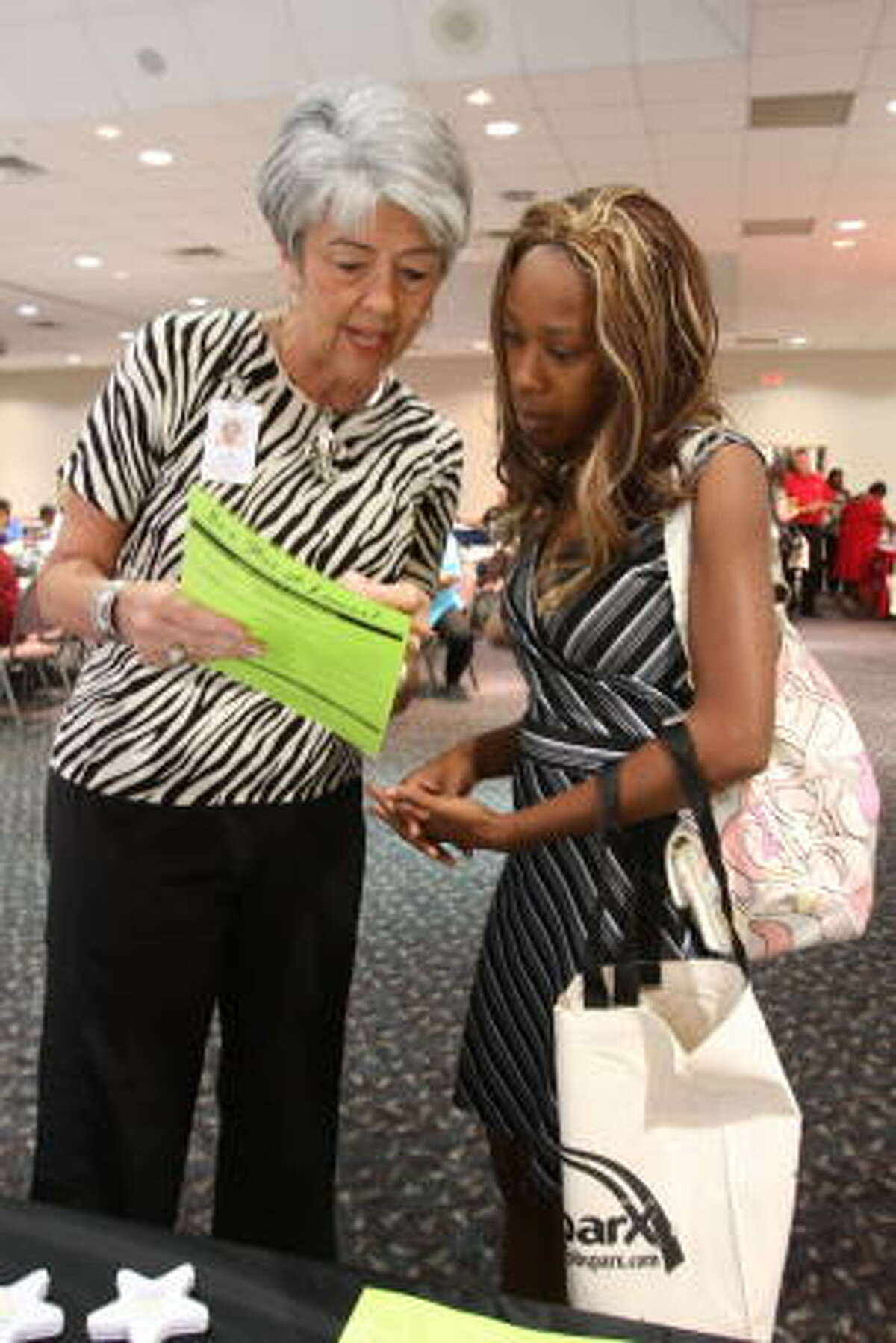 JOB FAIR: Fort Bend County held its third annual public sector career fair with other governmental agencies participating Sept. 29 at the Rosenberg Civic and Convention Center, 3825 Texas 36 S. Judy Adamson, human resource specialist for Lamar Consolidated Independent School District, shows a list of job openings at the district to Viviana Guerra of Rosenberg.