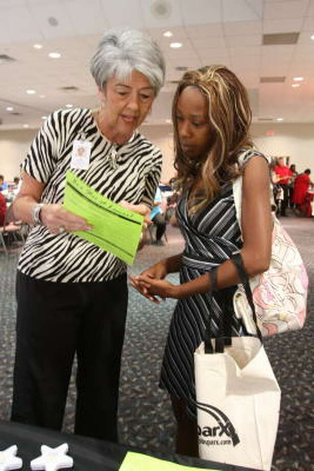 JOB FAIR: Fort Bend County held its third annual public sector career fair with other governmental agencies participating Sept. 29 at the Rosenberg Civic and Convention Center, 3825 Texas 36 S.  Judy Adamson, human resource specialist for Lamar Consolidated Independent School District, shows a list of job openings at the district to Viviana Guerra of Rosenberg. Photo: Suzanne Rehak, For The Chronicle