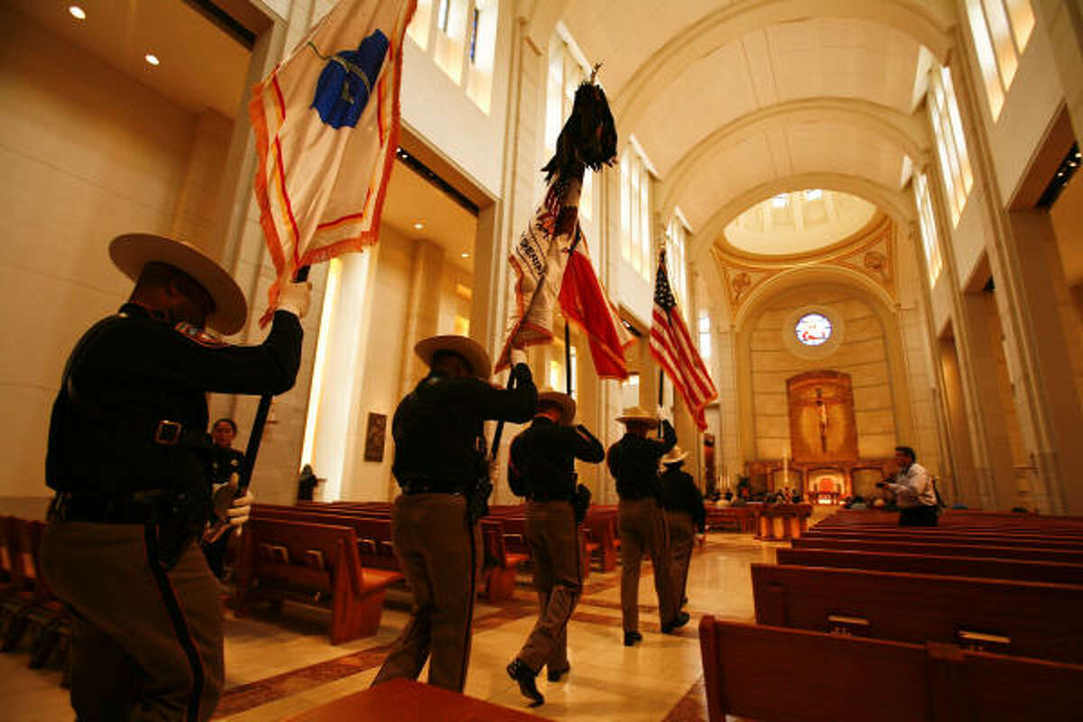 Members of the Harris County Sheriff 's Office Honor Guard enter the chapel of the Co-Cathedral of the Sacred Heart.
