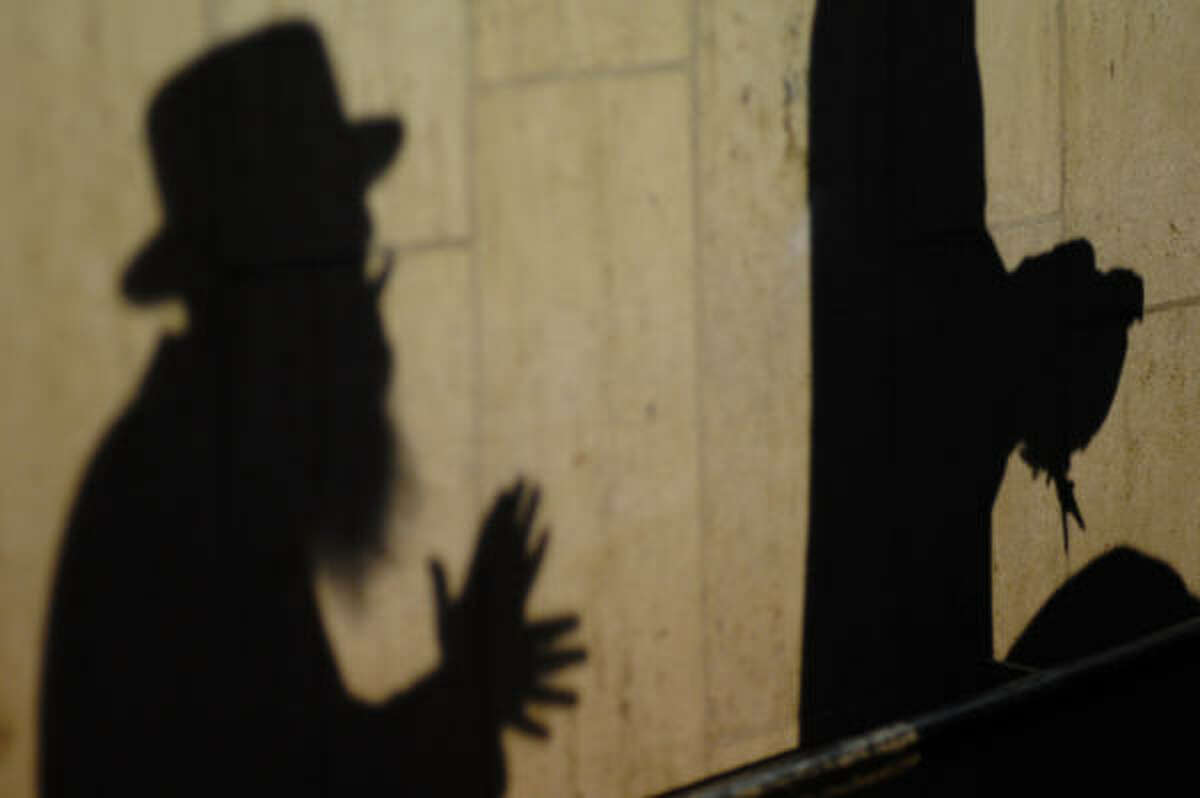 The shadow of two ultra-Orthodox Jewish men, one of them holding a chicken, are cast on a wall during the Kaparot ceremony in the costal city of Ashdod, early on September 27, 2009. According to Jewish beliefs, the ritual is supposed to transfer the sins of the past year to the chicken, and is performed before Yom Kippur. The chicken will then be slaughtered and donated to the poor.