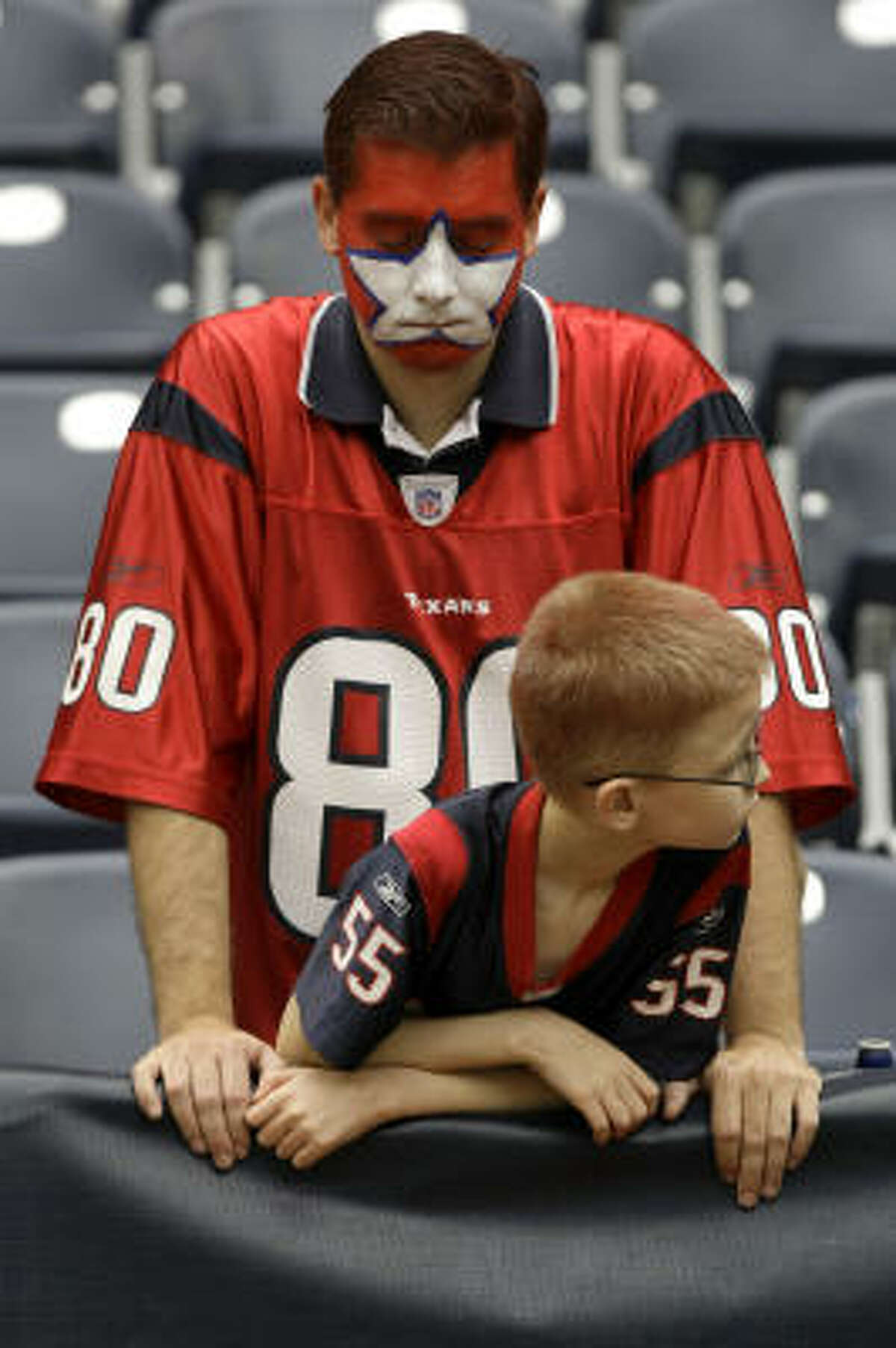 Chris Reid, with Joshua Reid, reacts to the Texans loss to the Jacksonville Jaguars 31-24.