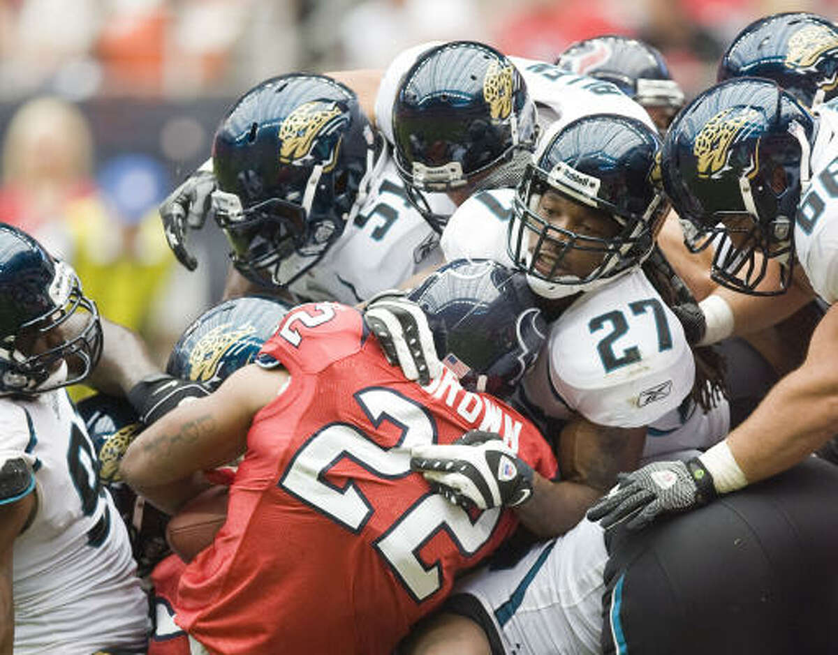 Texans running back Chris Brown is tackled by Jacksonville Jaguars defenders during the second quarter.