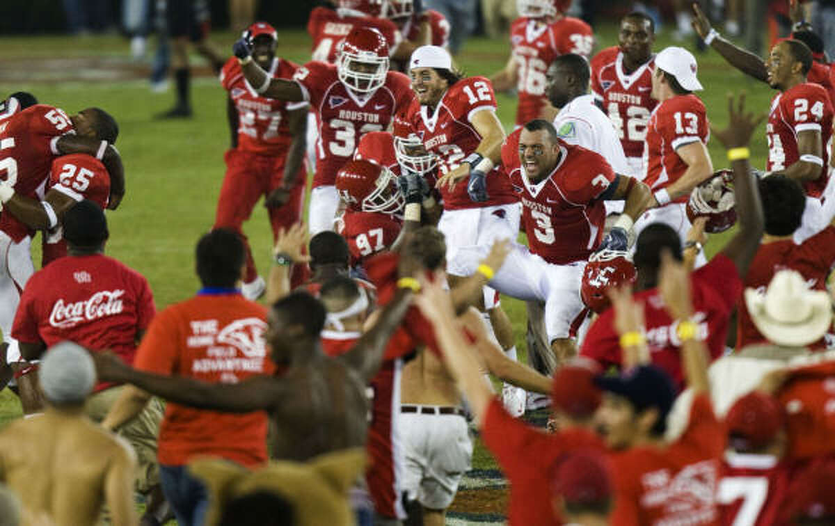 Houston player celebrate as the fans storm the field following the Cougars' victory over Texas Tech on Saturday at Robertston Stadium.
