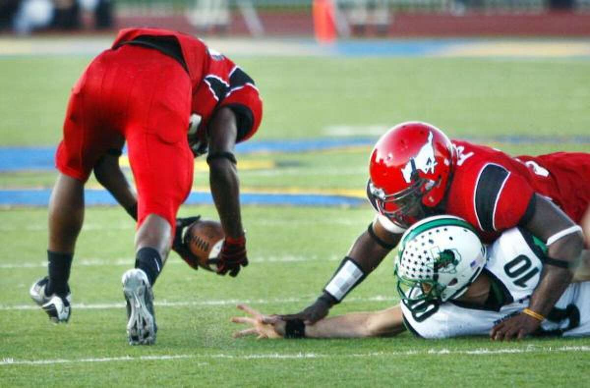 North Shore 28, Southlake Carroll 15 North Shore's Derrick Mathews (left) scoops up a bad snap that sailed over the head of Southlake Carroll quarterback David Piland, held down by North Shore's Jarrod Foster. Mathews took the turnover back for a touchdown during the first half.