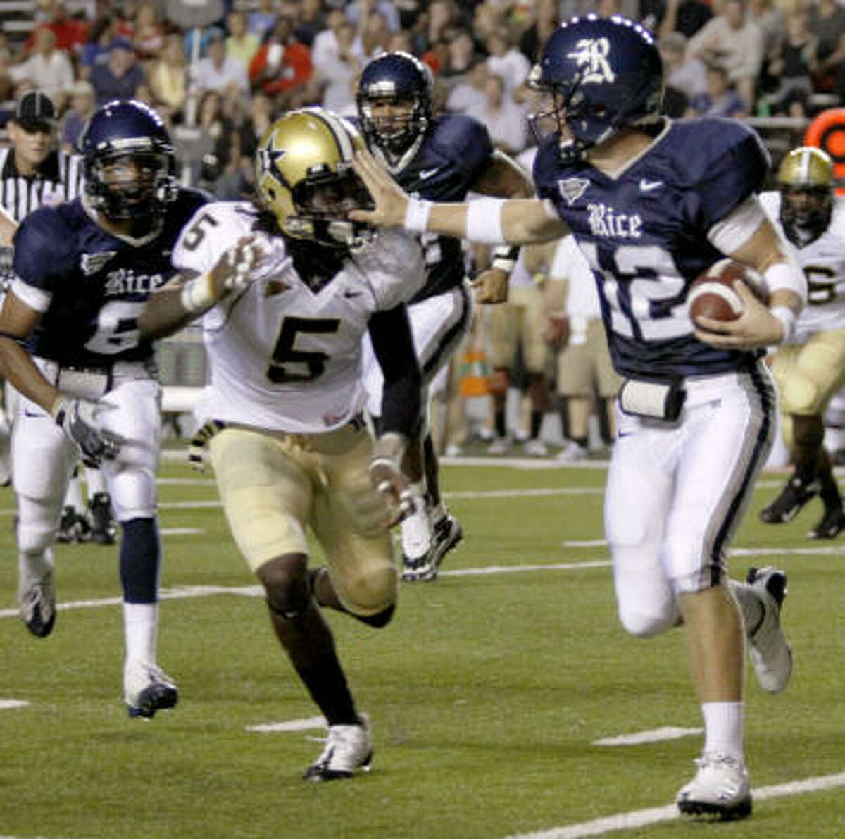 Rice Owls quarterback Ryan Lewis holds off Vanderbilt CB Myron Lewis during Rice's home football opener Saturday.
