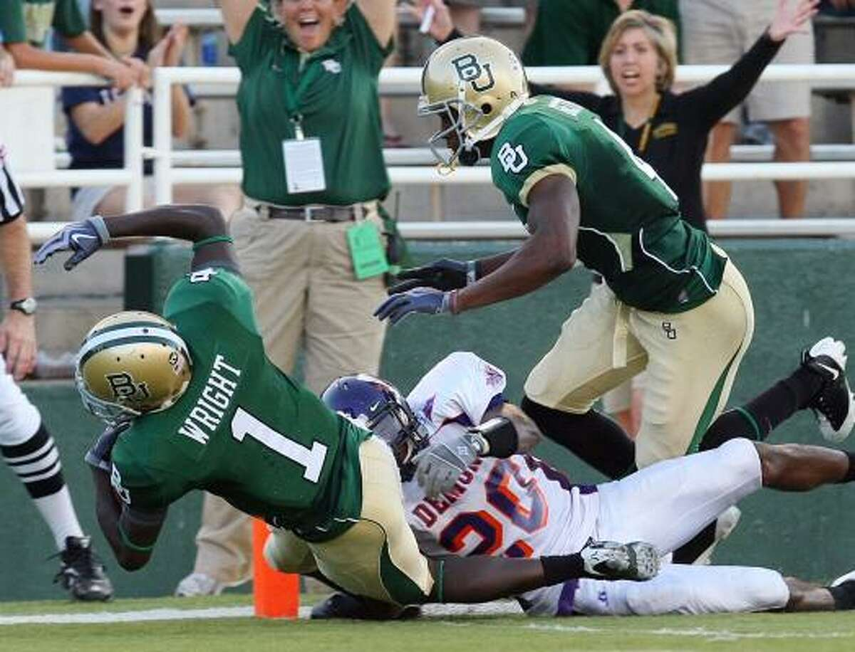 Baylor Kendall Wright (1) falls into the endzone past Northwestern State's Cortez Paige (20) for a first half touchdown Saturday in Waco.