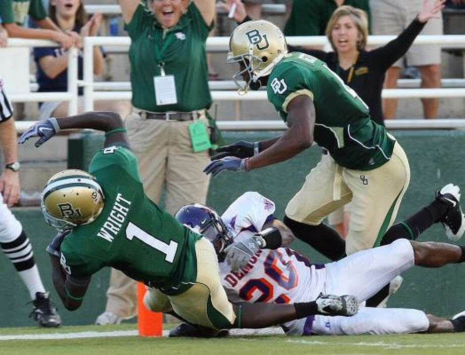 Baylor Kendall Wright (1) falls into the endzone past Northwestern State's Cortez Paige (20) for a first half touchdown Saturday in Waco. Photo: Jerry Larson, Associated Press