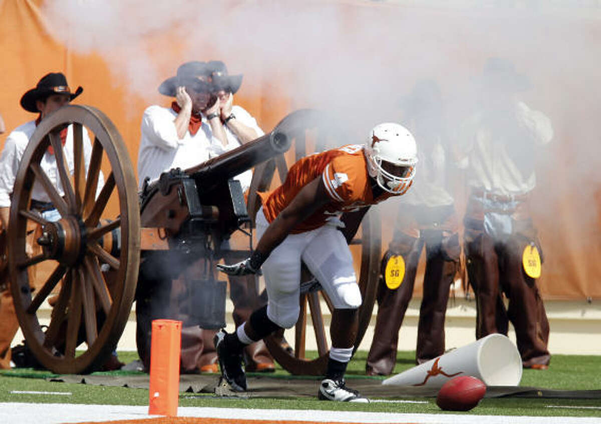Texas receiver Dan Buckner ducks his head as the UT cannon goes off right behind him after he scored a touchdown in the first half.
