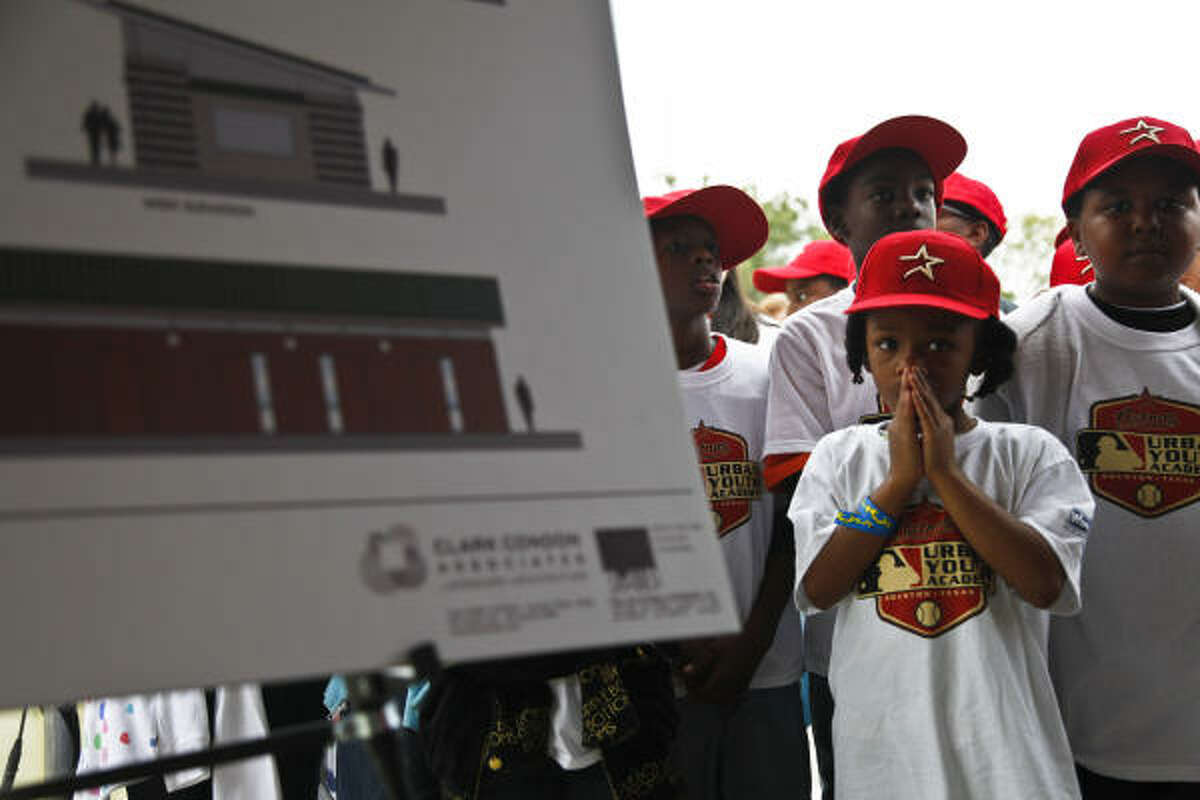Eight-year-old Maiyah Campbell stands near a mock up of a new building to be built at the future sight of the academy.