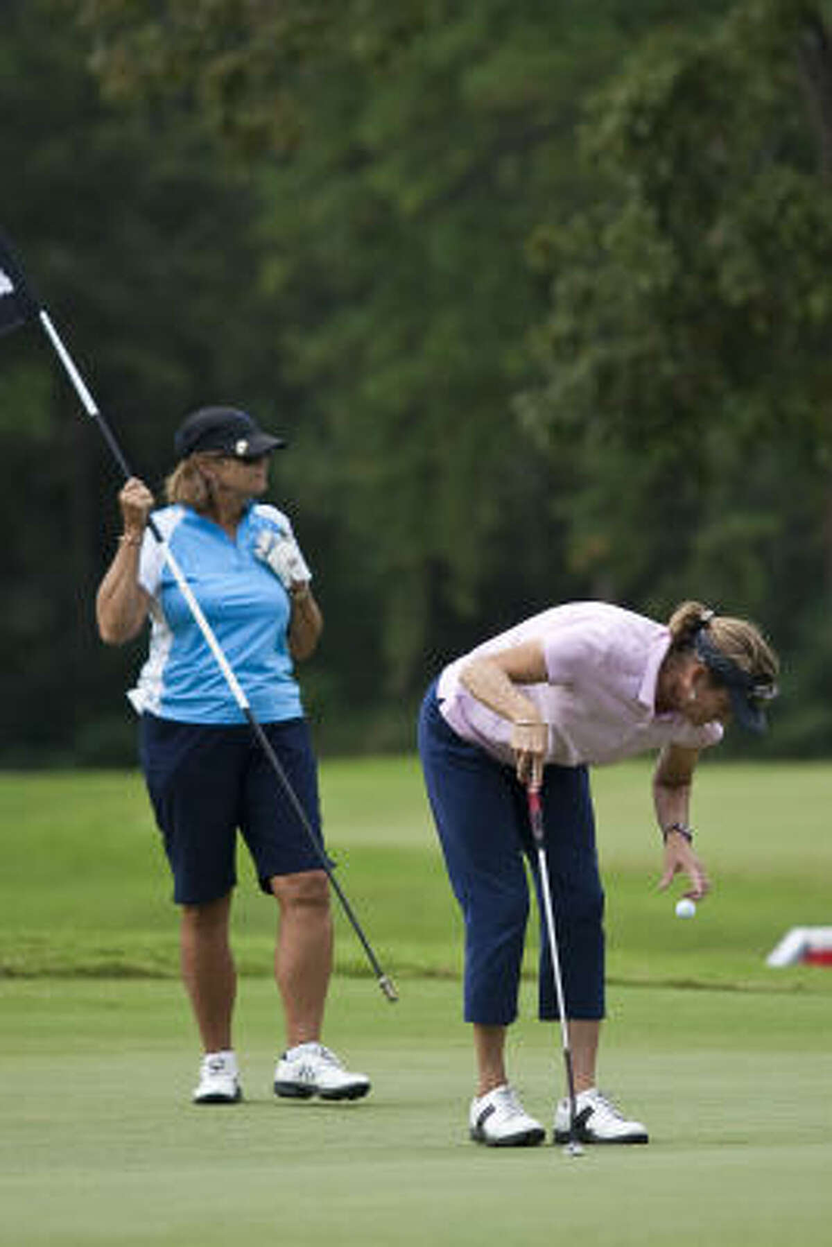 Marilyn Hardy retrieves her ball after sinking a putt on the 15th hole.