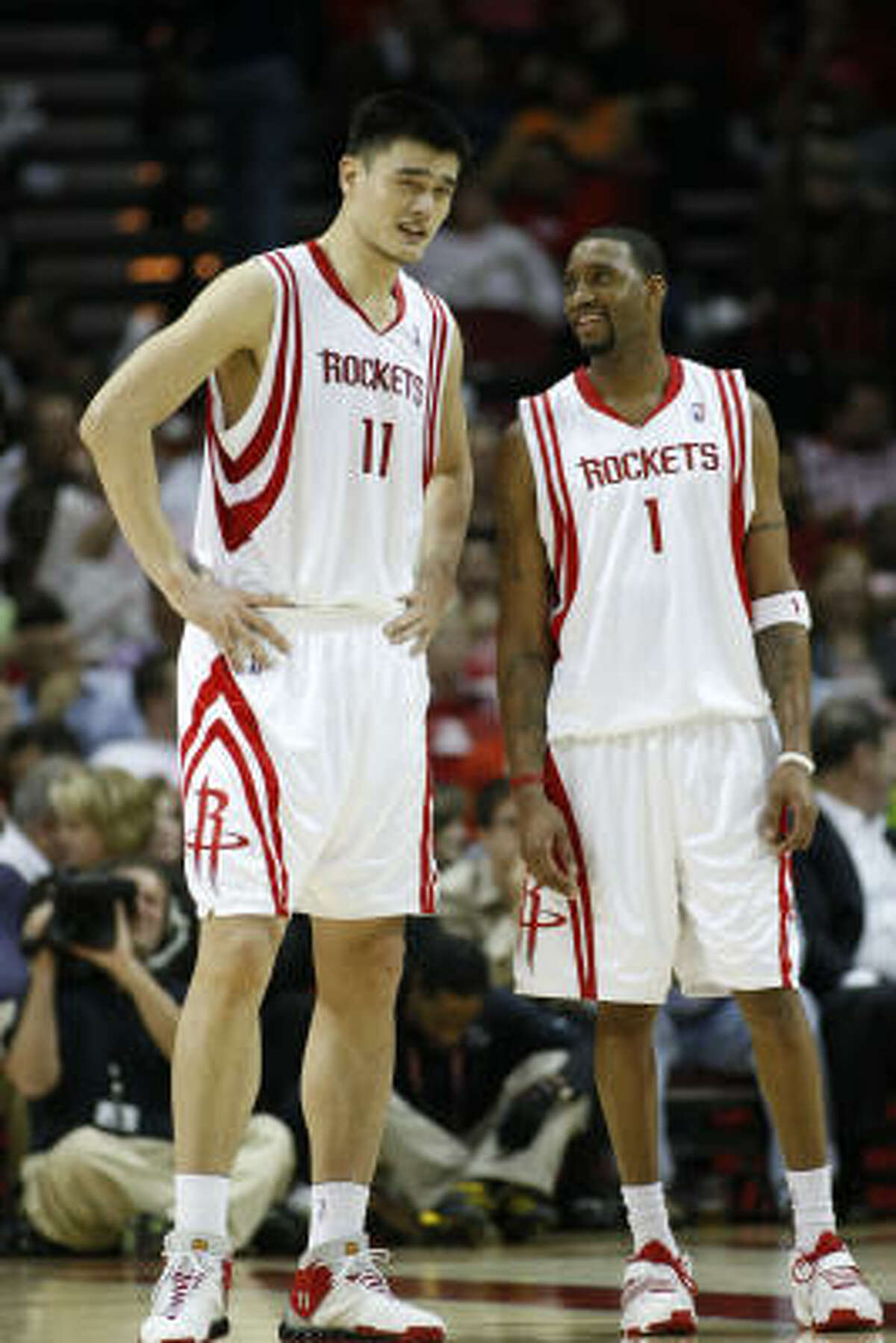 (2003-Present) Rockets center Yao Ming, left, shares a light moment with teammate Tracy McGrady.