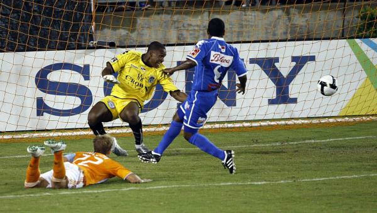 The Dynamo's Stuart Holden, left on ground, scores on a diving header past Arabe Unido goalkeeper Carlos Bejarano, center, and Nahil Carroll.