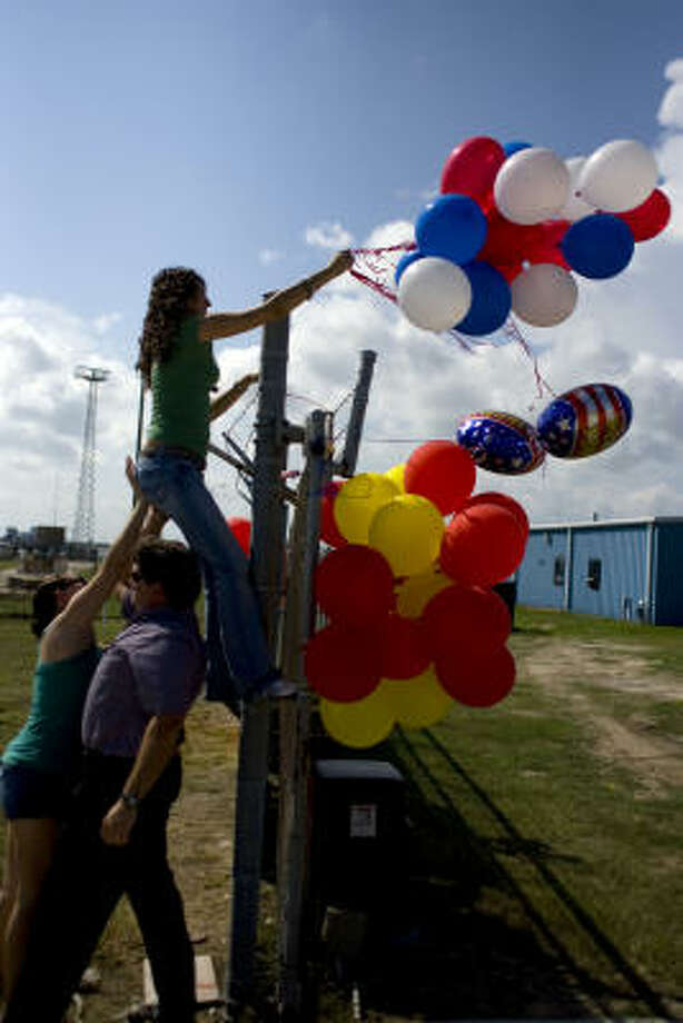 Tabatha Hinote, 22, sister of Marine Donald Hinote, gets A push from her father, Bruce Hinote, and Lois Wampler, the sister of Marine Ryan Wampler, as she hangs balloons on a fence to greet 52 Marines from the 3rd Platoon, Bravo Company, 4th Assault Amphibian Battalion based out of Galveston as they returned home from a six-month deployment in Iraq at the Marine Reserve Training Center Monday. Photo: Johnny Hanson, Chronicle