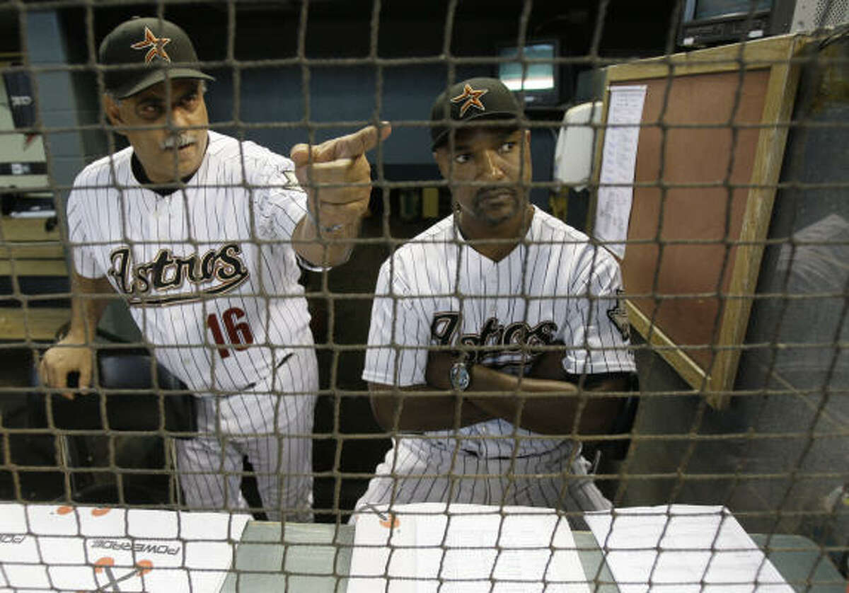 Astros bench coach with Ed Romero, left, and interim manager Dave Clark talk in the dugout before game against the St. Louis Cardinals.