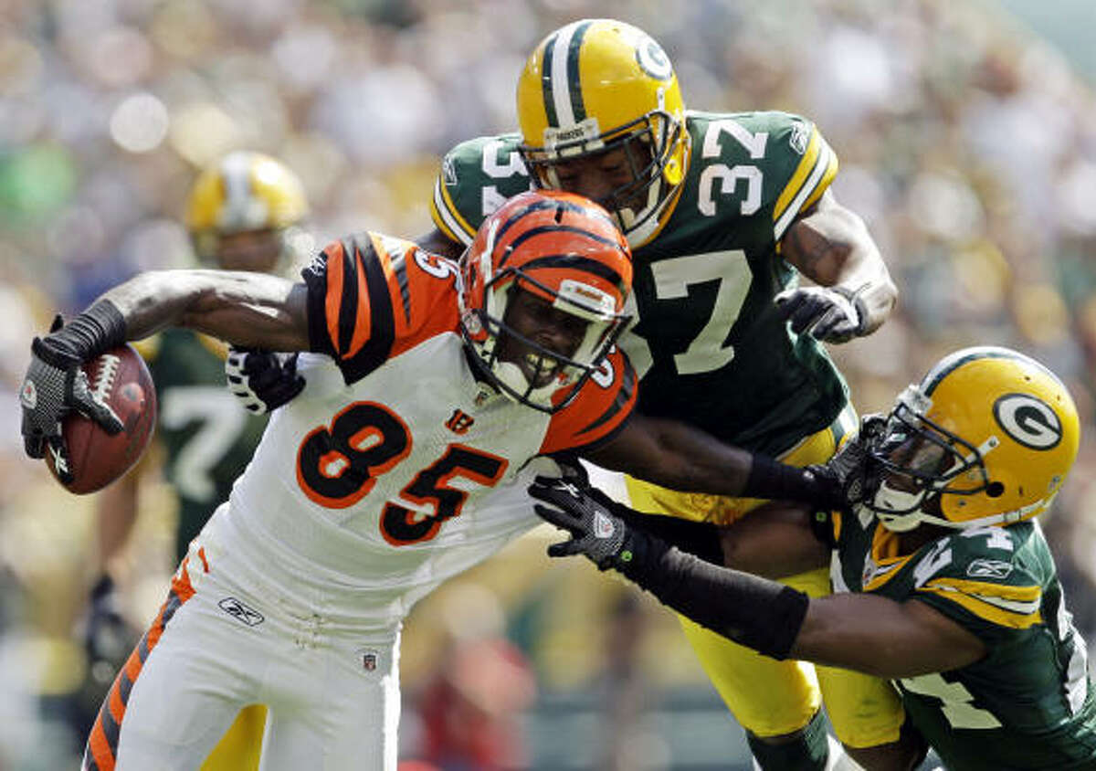 Bengals 31, Packers 24 Bengals wide receiver Chad Ochocinco (85) runs after a catch as Green Bay's Aaron Rouse (37) and Jarrett Bush (24) try to bring him down in the first half.