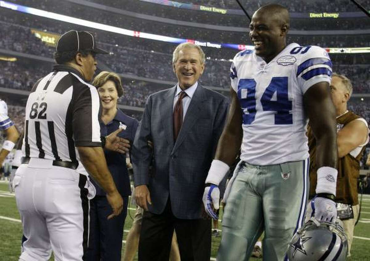 Field judge Buddy Horton (left) looks on as former First Lady Laura Bush, second from left, former President George W. Bush and Dallas Cowboys linebacker DeMarcus Ware (94) talk before Bush made the coin toss before the Cowboys' NFL football game against the New York Giants.