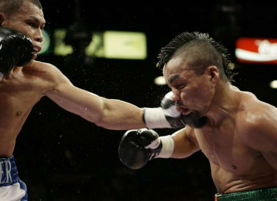 Chris John, left, retained his WBA featherweight title with an unanimous decision over Rocky Juarez on Saturday night, hanging on in the 12th round to win their second bout in seven months. Photo: Laura Rauch, AP