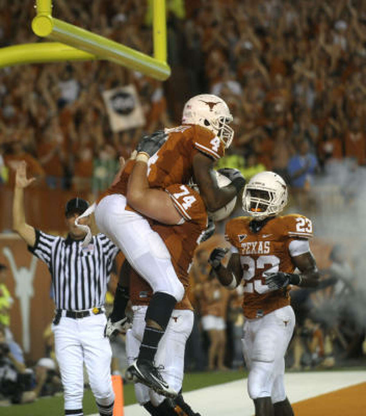 Texas receiver Dan Buckner, top, celebrates with guard Adam Ulatoski and running back Tre' Newton after scoring a second-half touchdown.