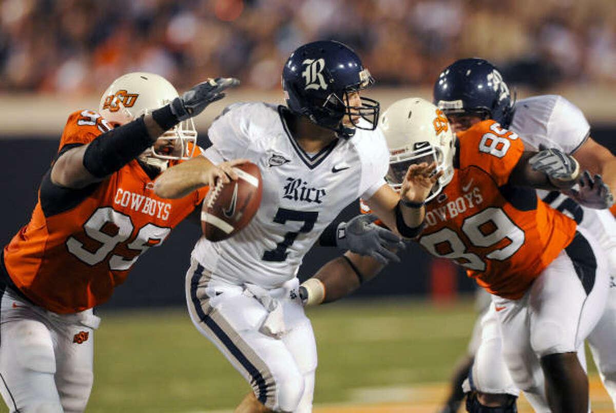 Oklahoma State defensive ends Richetti Jones, left, and Nigel Nicholas close in on Rice quarterback Nick Fanuzzi.