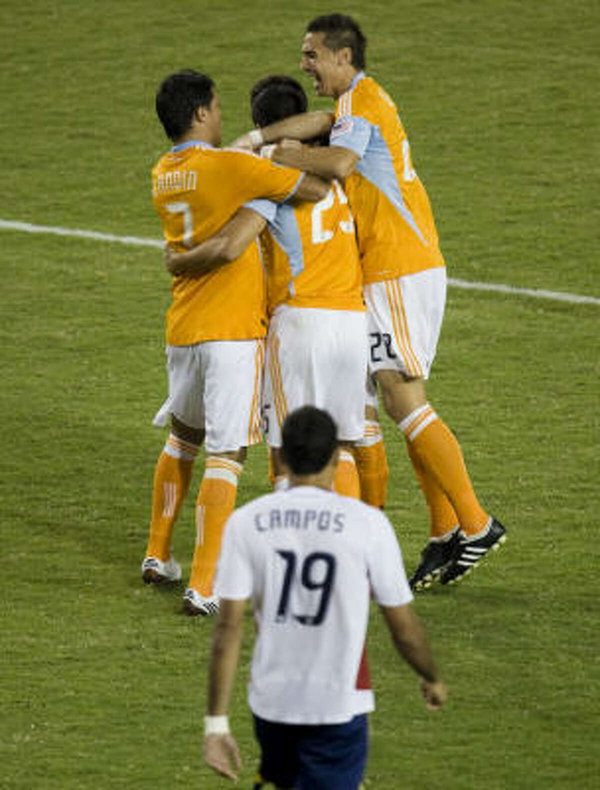 Dynamo forward Brian Ching (25) celebrates with teammates Luis Angel Landin (7) and Geoff Cameron (20) after Ching scored in the second minute of the first half.