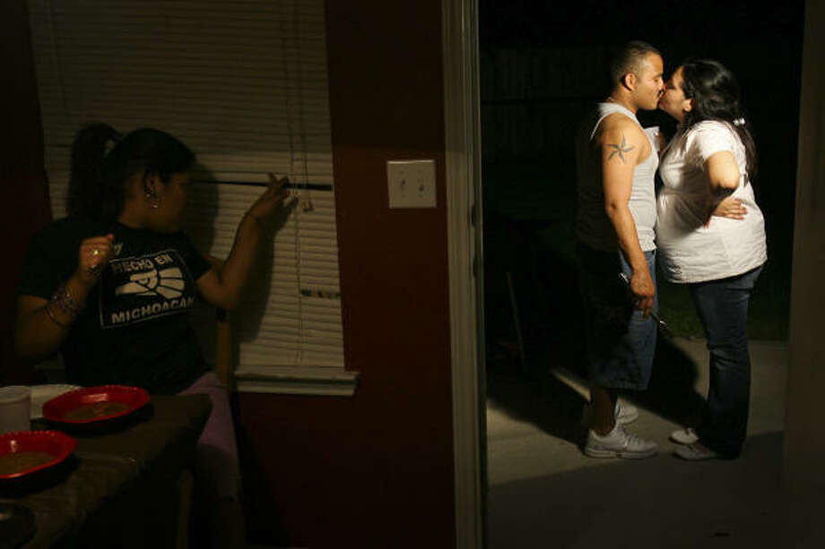 """Elizabeth Gonzalez peeks out the window as her aunt Laura Gonzalez kisses her boyfriend  during a party in August. """"I love you,"""" says Spc. Antonio Hernandez.  """"I love you more,""""  Gonzalez replied. Photo: Mayra Beltran, Chronicle"""