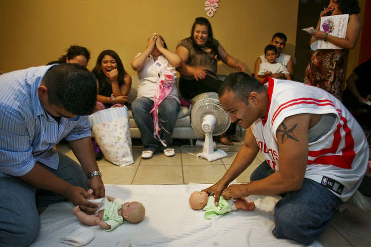 Hernandez competes with David Carreon to see who can change diapers faster during a baby shower game as Gonzalez and guests laugh at his lack of experience. Hernandez is one of the 3,500 soldiers of the Texas National Guard's 72nd Infantry Brigade Combat Team who are preparing for a year-long deployment, including nine months in Iraq