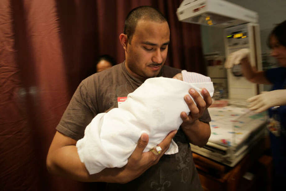 "Hernandez cradles his newborn daughter after the delivery. ""I knew it was coming but when you actually see it?  Whoa, my God ... It's something that I'll carry with me while I'm training and while I'm over there."" Photo: Mayra Beltran, Chronicle"