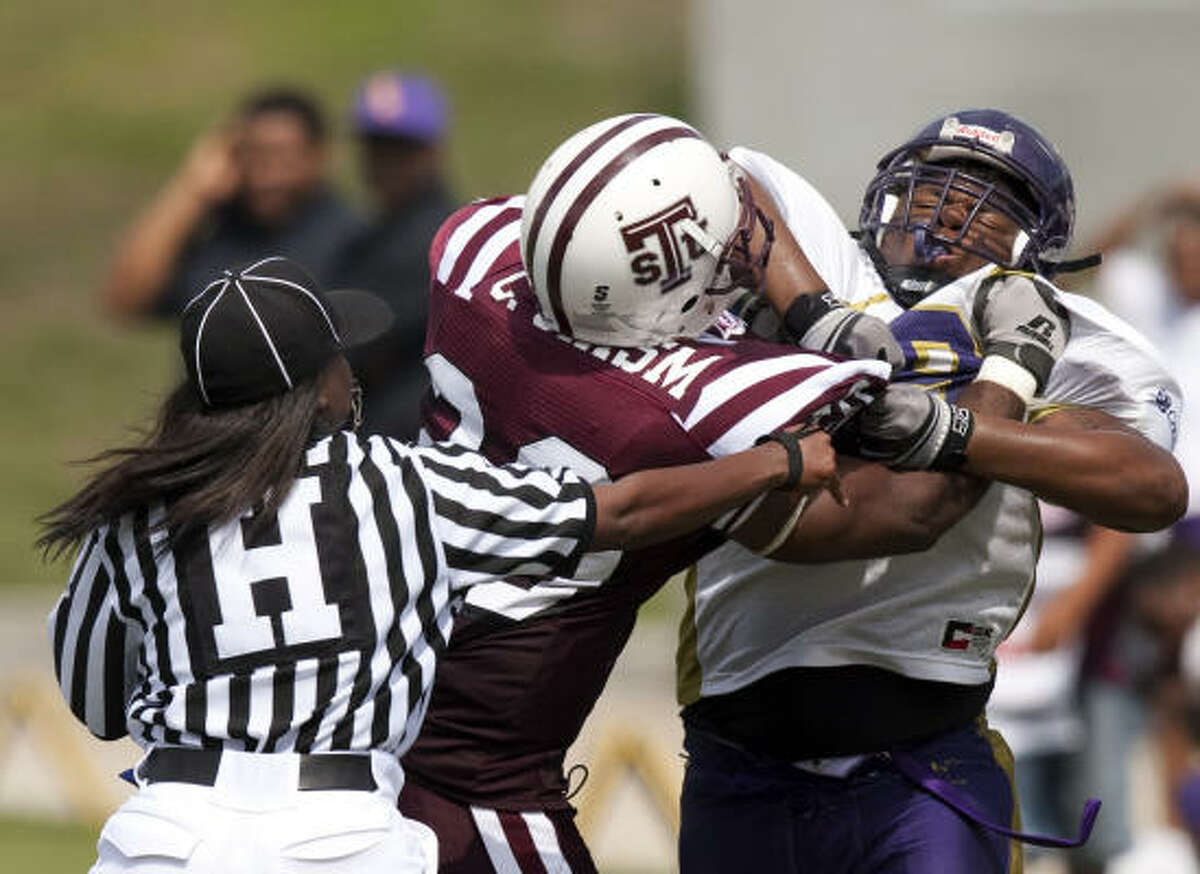 Head linesman Yvonda Lewis reaches in to separate TSU defensive back Carl Chism from Texas College running back Alvin Samuel as they tussle during the third quarter.