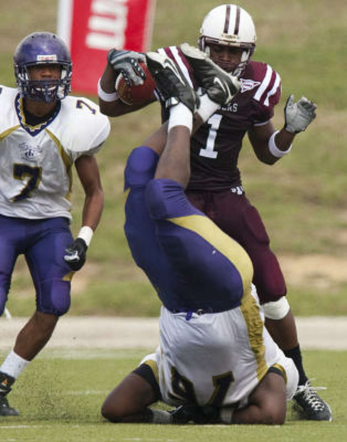 TSU receiver Joe Anderson tries to avoid Texas College defender Brandon Bishop, who is overturned trying to make the tackle during the third quarter of the Tigers' 75-6 victory against Texas College at Delmar Stadium on Saturday.