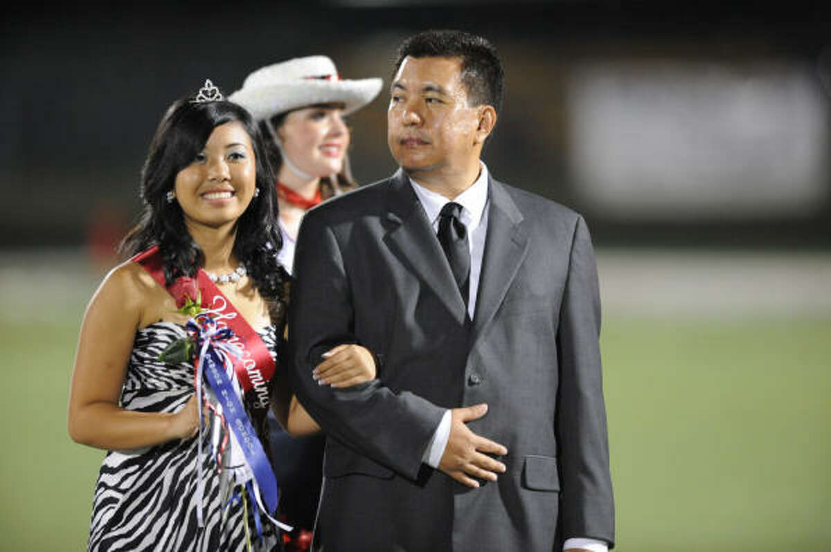 Dawson junior Angelene Superable is escorted by her dad, Angel Superable, during the Homecoming Queen ceremony.