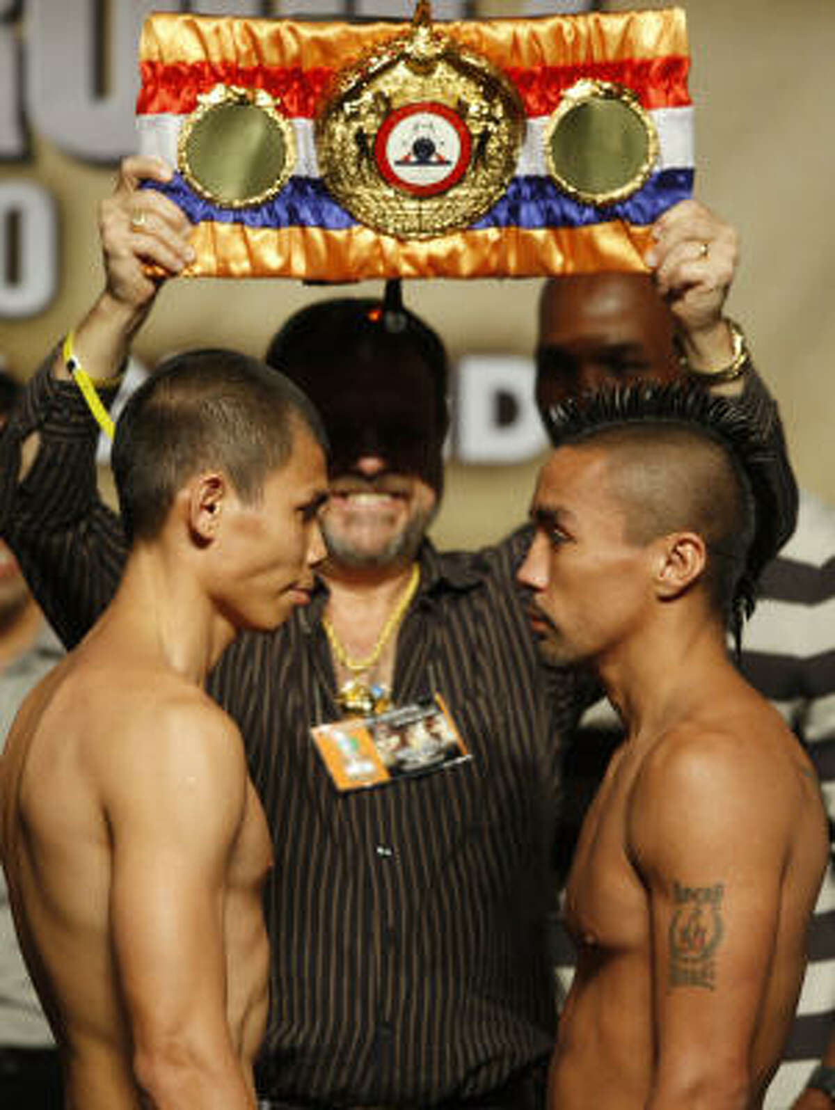 Houston's Rocky Juarez faces WBA featherweight champion Chris John, left, during their official weigh-in for a Saturday fight. For more on Juarez, click here.