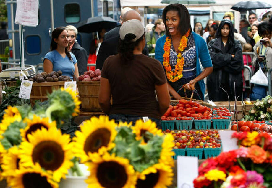 First lady Michelle Obama greets vendors as she shops for fresh produce at the opening of the new farmer's market. The new market will be open every Thursday for the next seven weeks.  More: More about the new market | Houston-area farmer's markets | Houston Plant Database | HoustonGrows.com Photo: Win McNamee, Getty Images
