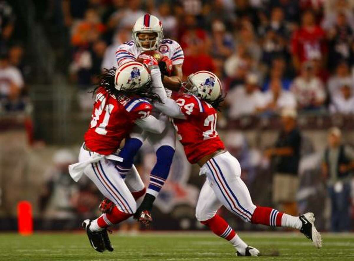 New England Patriots 25, Buffalo Bills 24 Bills receiver Josh Reed, top, catches a pass between Patriots' Brandon Meriweather (31) and Jonathan Wilhite (24) during the first half of play.