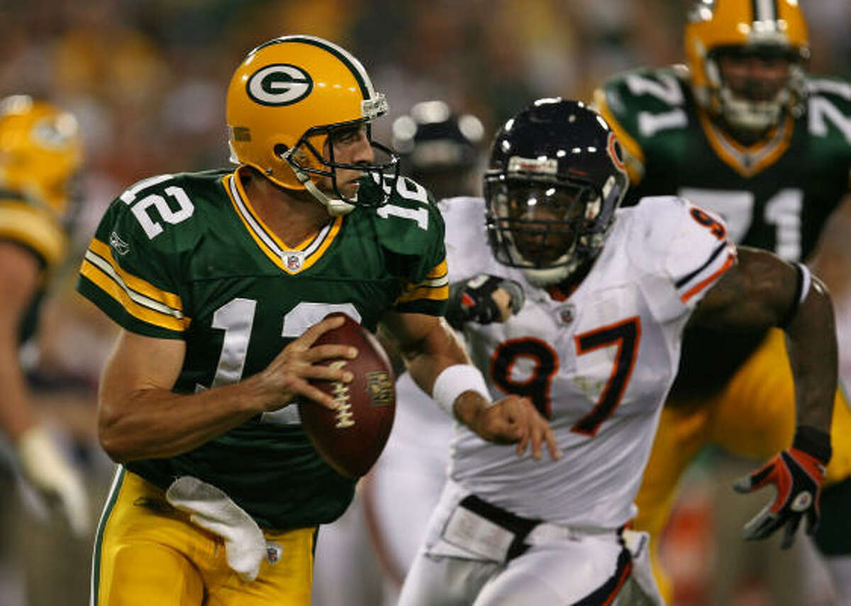 Green Bay Packers 21, Chicago Bears 15 Packers quarterback Aaron Rodgers, left, runs to avoid Mark Anderson of the Chicago Bears.