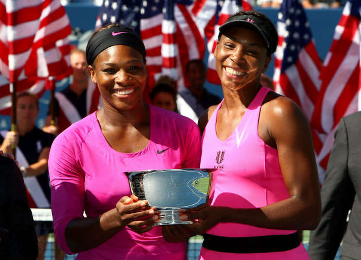 Serena Williams, left, and Venus Williams pose with the championship trophy Monday, Sept. 14, after defeating Cara Black and Liezel Huber 6-2, 6-2.