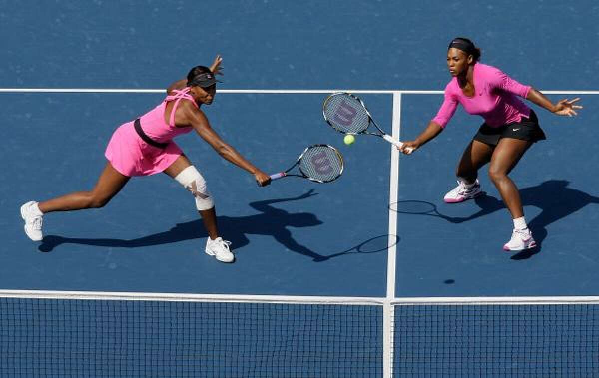 Venus Williams, left, and Serena reach to hit a shot from Liezel Huber.