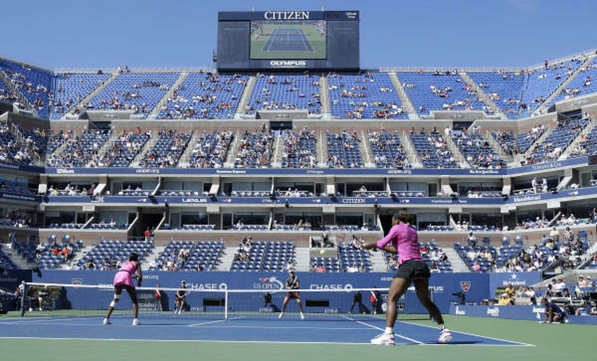 Serena Williams, right, hits a shot from the baseline.