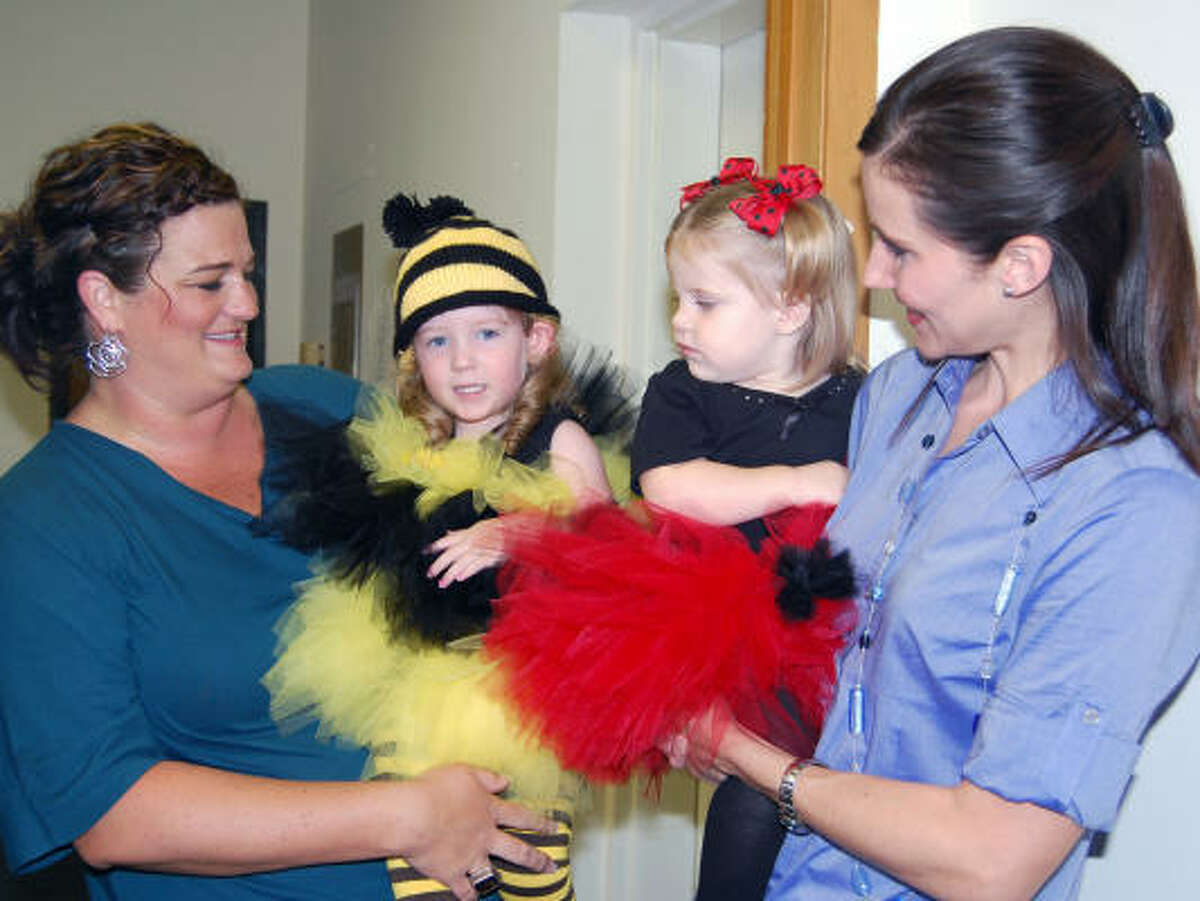 Karys Kinder, 2, and her mom Kamela wait to go onstage to model a bumblebee Halloween costume, while ladybug Julianne Melancon, 18 months, waits with her mom, Jada. The event was presented by Sassy Pants Studio in Friendswood.