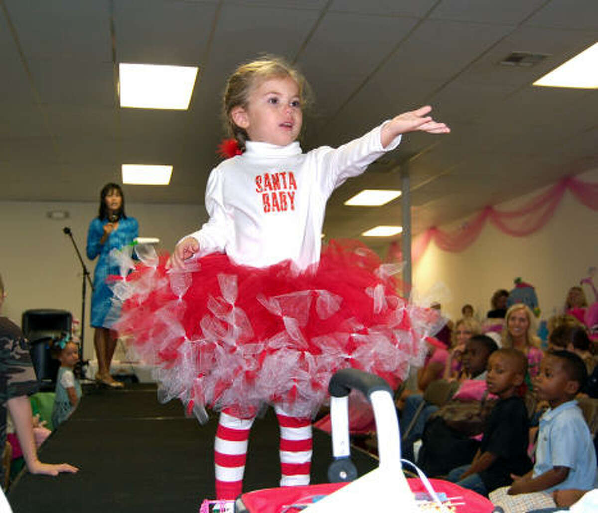Mallory Rollins, 4, throws a kiss to the audience in her Christmas outfit at the Sept. 12 show. Children modeled back-to-school, Halloween, Thanksgiving and Christmas fashions.