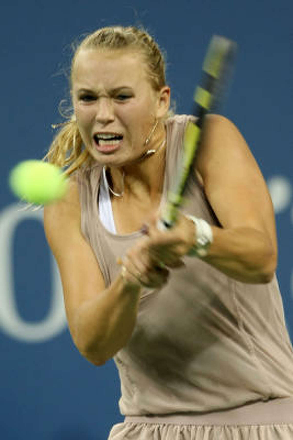 Caroline Wozniacki of Denmark returns a shot to Kim Clijsters of Belgium.