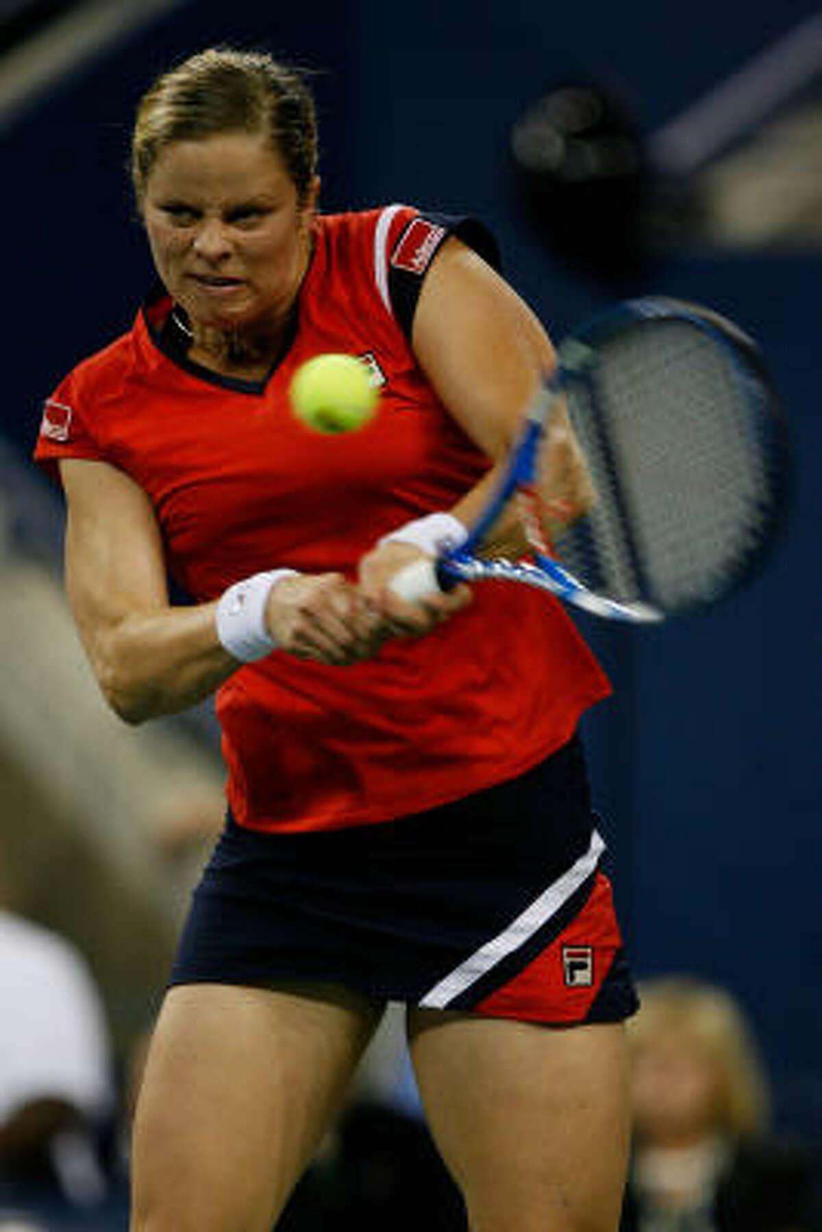 Kim Clijsters of Belgium returns a shot to Caroline Wozniacki of Denmark.