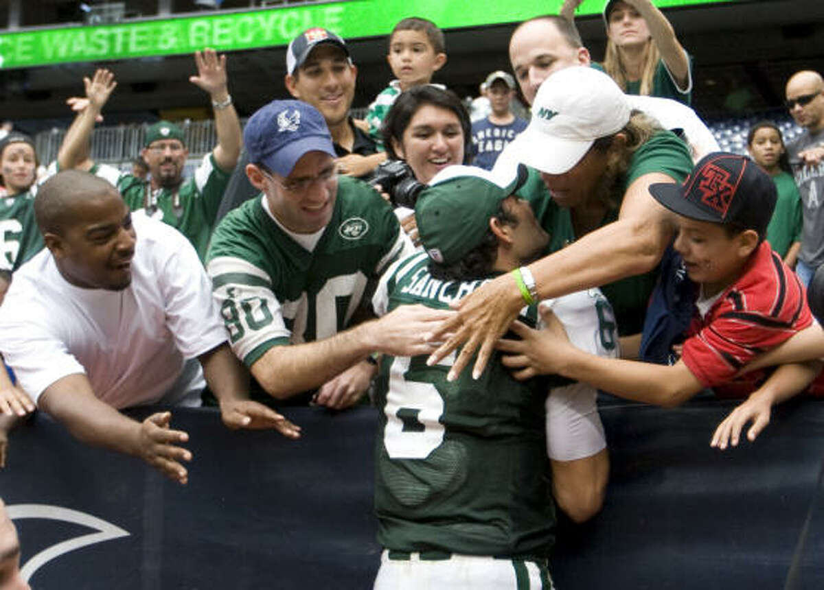 Jets quarterback Mark Sanchez (6) leaps into the stands to celebrate his team's 24-7 win over the Texans on Sunday at Reliant Stadium.