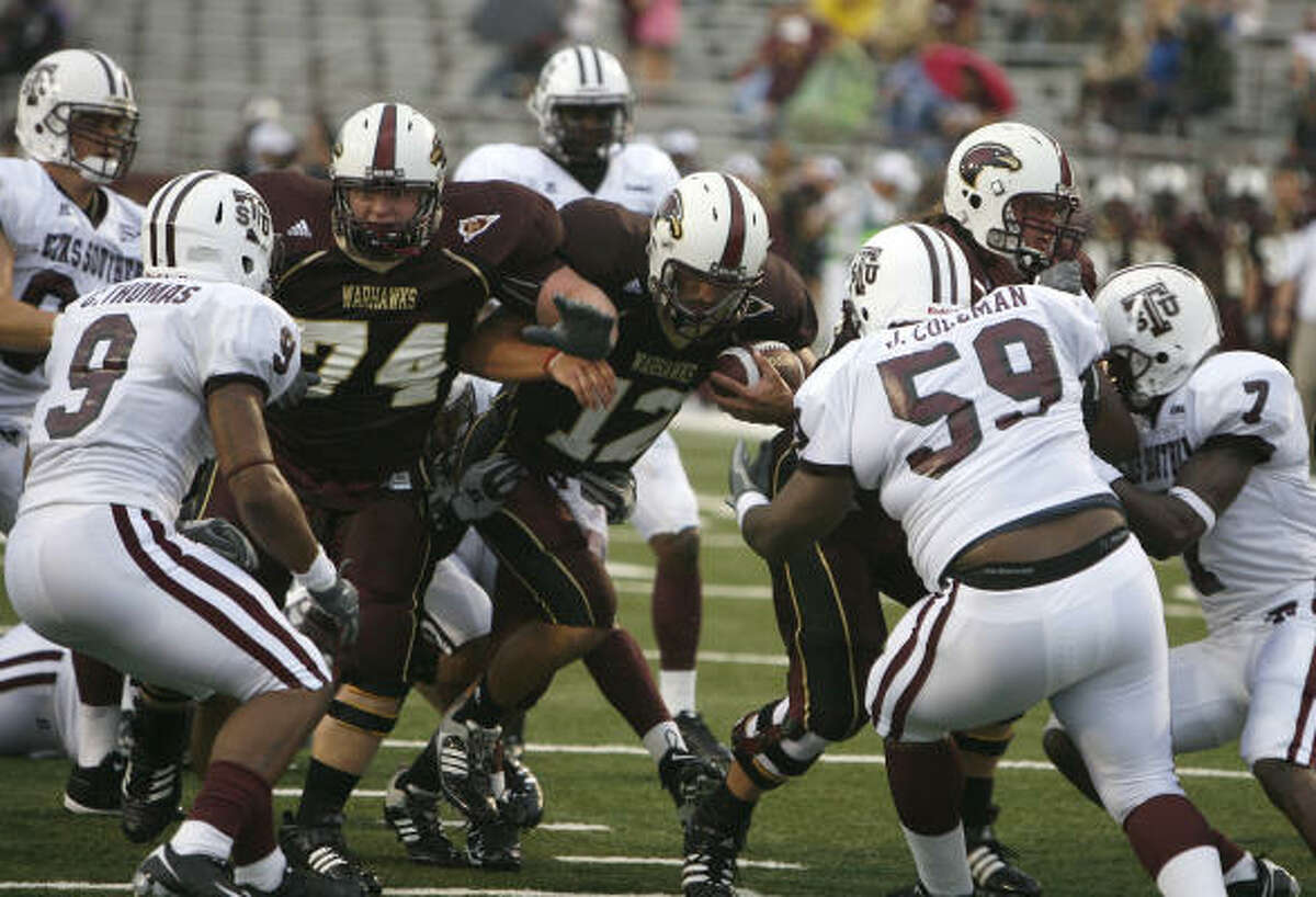 University of Louisiana at Monroe offensive lineman Andrew Stout and his teammates makes room for quarterback Trey Revell (12).