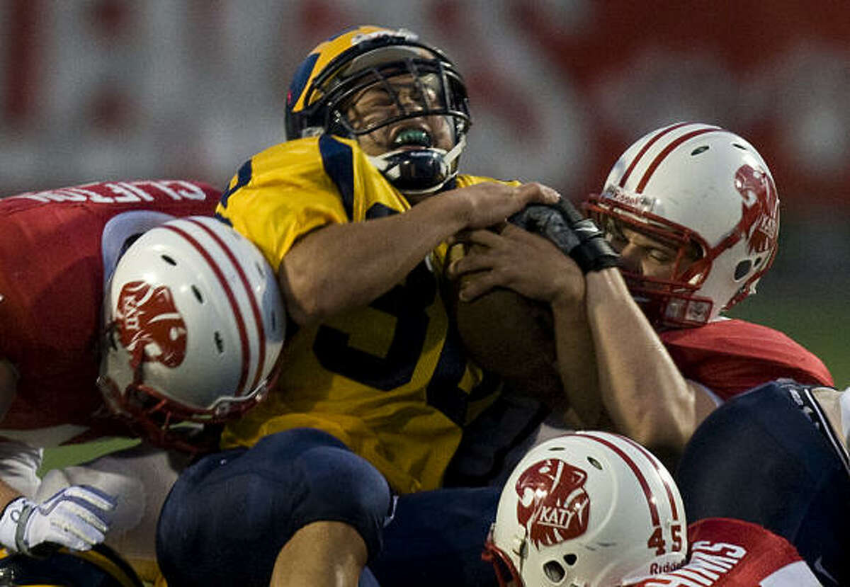 Bellevue running back David Nguyen is tackled by Katy defenders Tyler Adams (90), right, and linebacker Grant Cliffton (41).