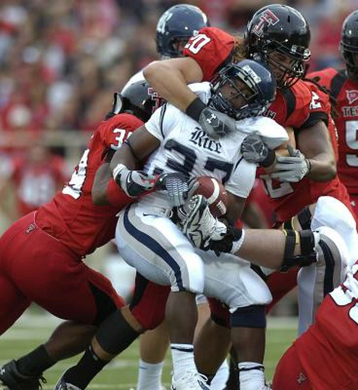 Texas Tech's Bront Bird (20) and Marlon Williams (39) wrap up Rice's Tyler Smith during Saturday night's game in Lubbock.