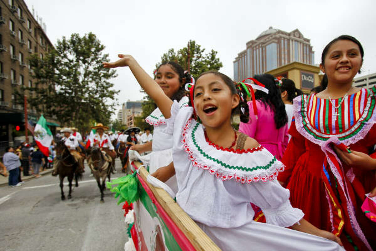 Ruby Trego (10) (left), Sandra Moreno (8) (center) and Janette Duarte (12) wave to the crowd during the 41st Annual Fiestas Patrias International Parade through downtown Houston.