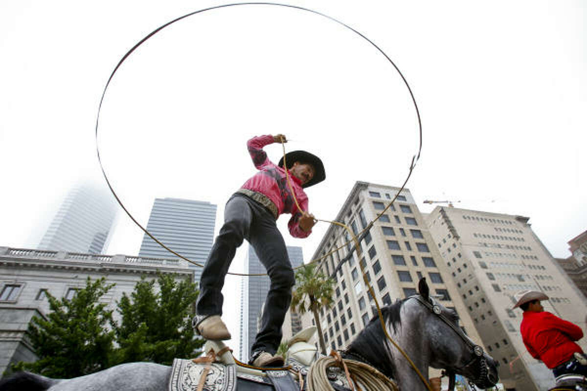 Clemente Flores performs with his lasso while standing on top of his horse during the 41st Annual Fiestas Patrias International Parade.