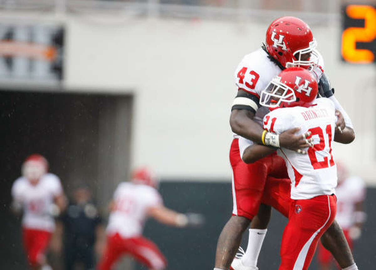 Houston defensive end Tyrell Graham (43), left, and cornerback Brandon Brinkley celebrate after forcing a turnover in the fourth quarter.