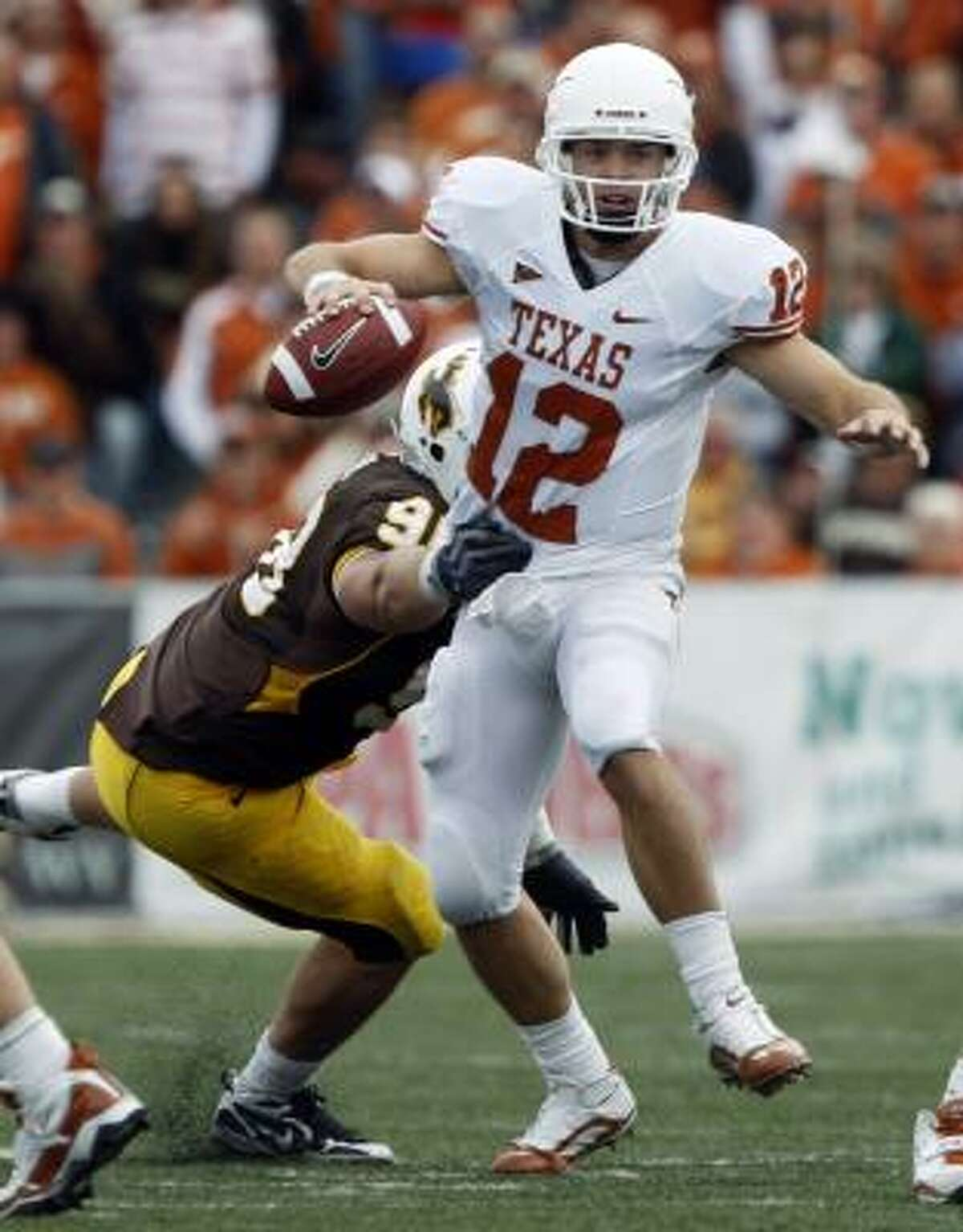 Texas quarterback Colt McCoy eludes Wyoming defensive end Mitch Unrein as he scrambles out of the pocket during the third quarter of their 41-10 victory.
