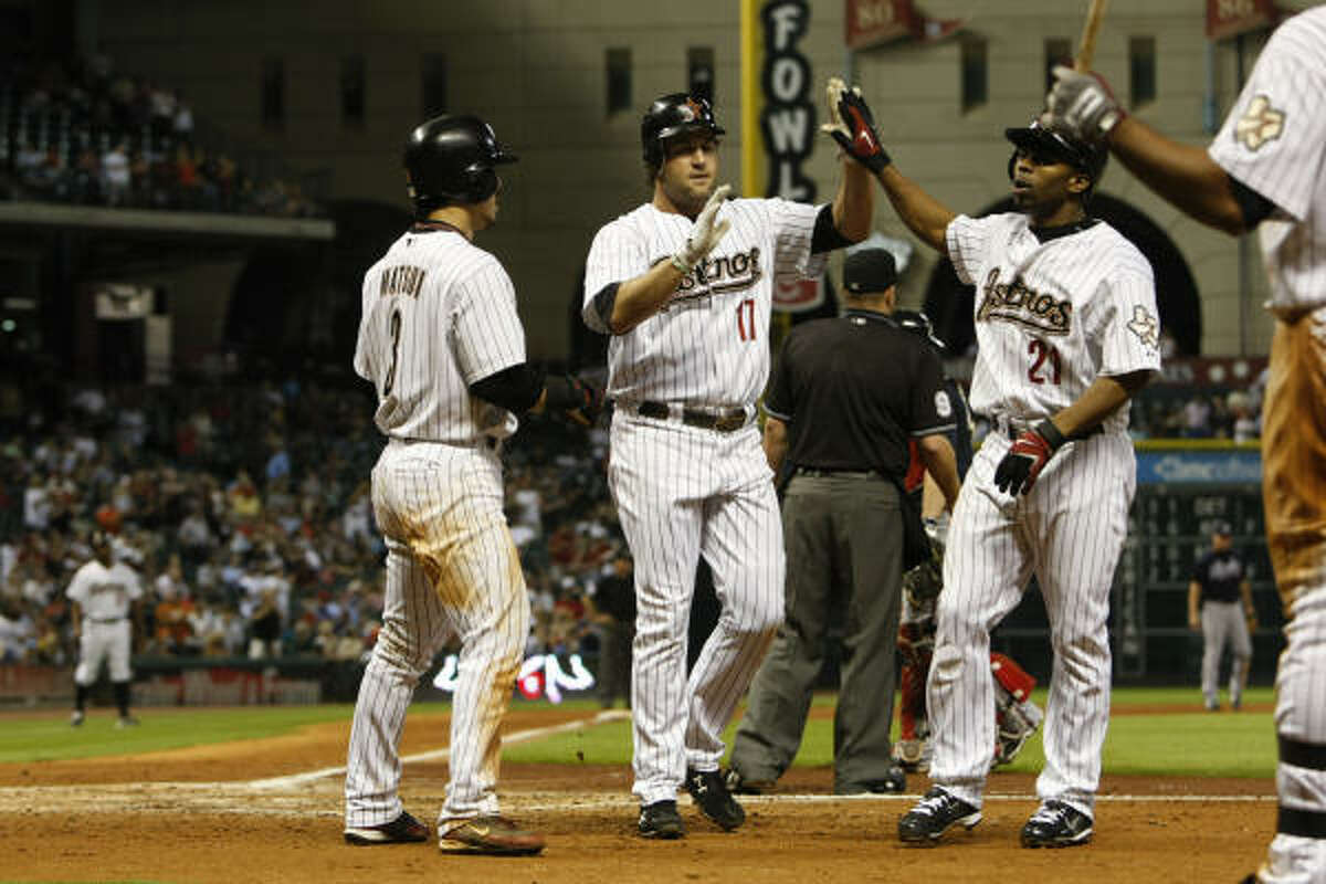 Lance Berkman (17) is greeted at home plate by Kazuo Matsui (left) and Michael Bourn after hitting a three-run home run in the third inning.